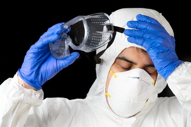 Covid-19. uitgeputte dokter, in persoonlijke beschermingsmiddelen, bezorgd als het coronavirus besmette gevallen en dodental stijgt. emotionele stress van gezondheidswerkers.