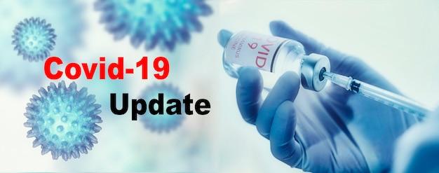 Covid-19 update-tekst met arts in medische handschoenen met een spuit op de achtergrond van zijn handen. covid-19 of coronavirus-concept