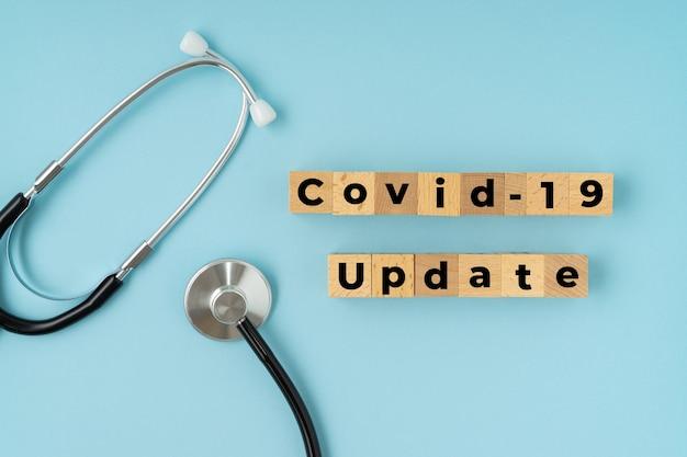 Covid-19 update-tekst met stethoscoop op blauw corona-virusconcept.