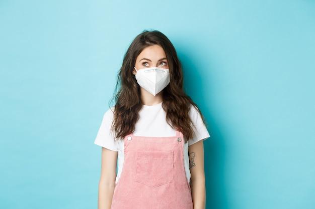 Covid-19, vaccinatie en quarantaineconcept. jonge vrouw met een medisch masker, een gasmasker dragend en kijkend naar het logo in de linkerbovenhoek, blauwe achtergrond.