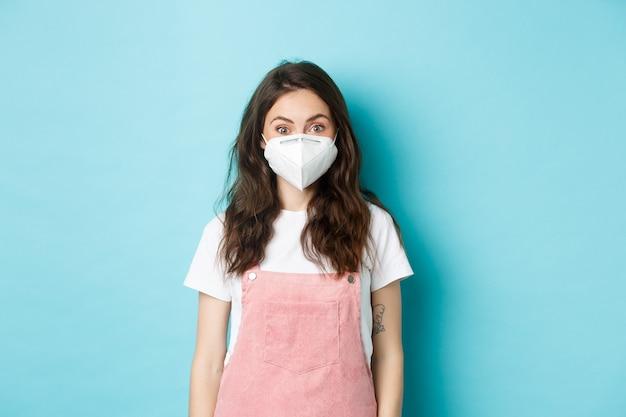 Covid-19, vaccinatie en quarantaineconcept. vrolijke vrouwelijke student die een gasmasker draagt om te voorkomen dat ze het coronavirus oplopen, sociale afstand nemen tijdens wereldwijde pandemie, blauwe achtergrond.