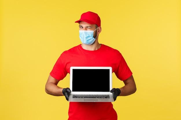 Covid-19, veilig winkelen, expreslevering en concept voor het volgen van bestellingen. knappe koerier in rood uniform, medisch masker en handschoenen, knipoogcamera en paginasite op laptopscherm.