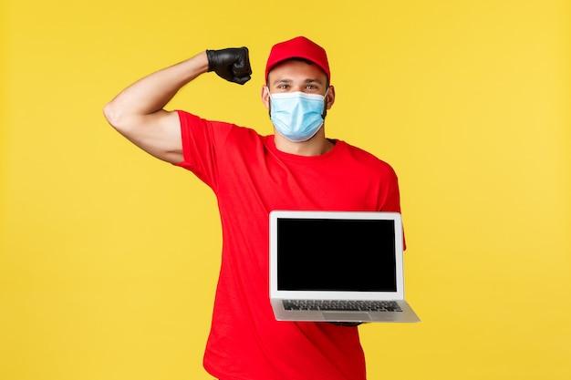 Covid-19, veilig winkelen, expreslevering en concept voor het volgen van bestellingen. sterke knappe koerier in rood uniform en medisch masker, flex biceps en laptopscherm, glimlachend