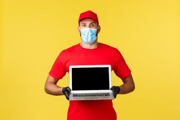 Covid-19, veilig winkelen, expreslevering en concept voor het volgen van bestellingen. verrast en onder de indruk koerier in rood uniform en medisch masker met geweldige advertenties op laptopscherm