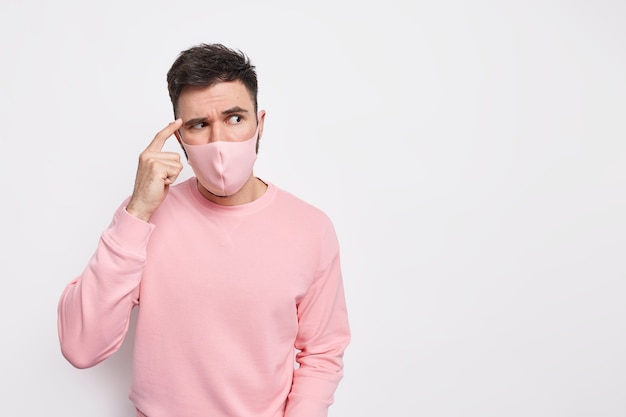Covid 19 virus en gezondheidszorgconcept. serieuze man houdt vinger op tempel geconcentreerd opzij met serieuze uitdrukking draagt beschermend masker tijdens quarantaine coronavirus