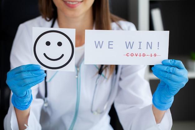 Covid-19, vrouwelijke arts houdt een formulier vast met de tekst die we winnen.
