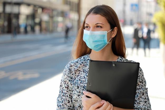 Covid-19 wereldwijde economische crisis werkloos meisje medisch masker op zoek naar een baan in de straat met curriculum vitae