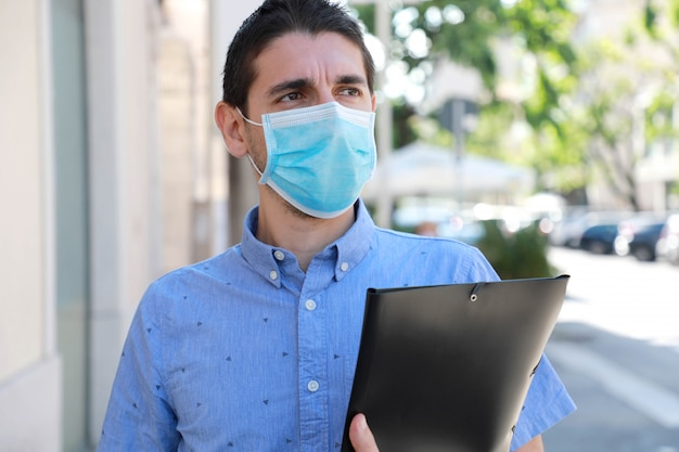 Covid-19 wereldwijde economische crisis werkloze jongeman met masker op zoek naar een baan die door de stad loopt terwijl hij zijn curriculum vitae levert