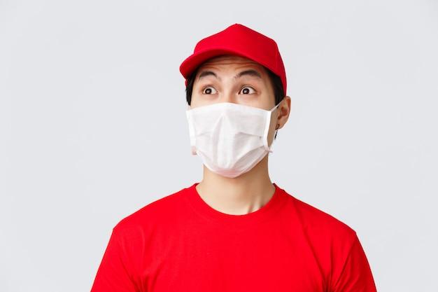 Covid-19, zelfquarantaine online winkelen en bezorgen concept. opgewonden en onder de indruk koerier in medisch masker en uniforme rode pet, t-shirt, verbaasd staren linksboven, grijze achtergrond