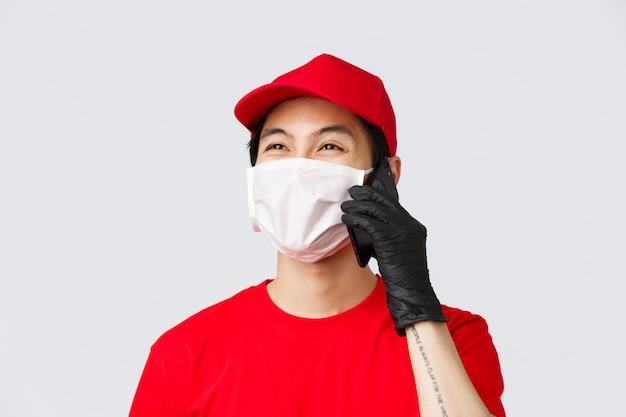 Covid-19, zelfquarantaine online winkelen en bezorgen concept. vriendschappelijke jonge aziatische koerier in medisch masker en beschermende handschoenen, die cliënt roepen, klant telefoneren beantwoorden, glimlachende, grijze achtergrond