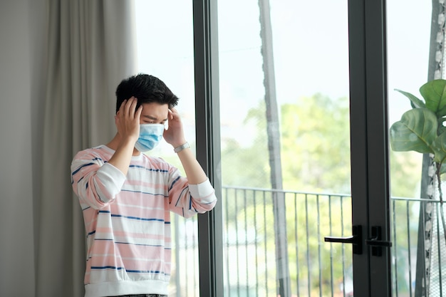 Covid-19. zieke man van coronavirus die door het raam kijkt en maskerbescherming draagt en thuis herstelt van de ziekte.