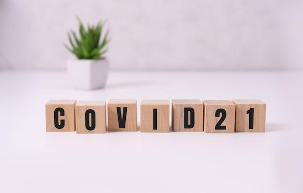 Covid 21 anno 2021. houten kubussen met tekst.