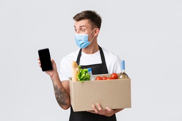 Covid contactloos winkelen en boodschappen bezorgen concept knappe verkoper in medisch masker suggereert ...