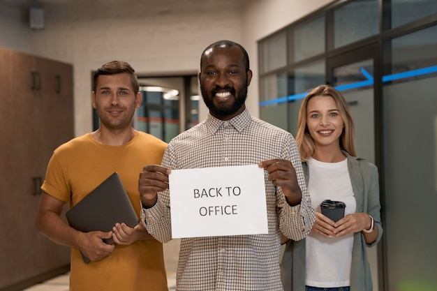 Covid en zakelijke jonge vrolijke afrikaanse kantoormedewerker die papier met tekst terug naar kantoor laat zien