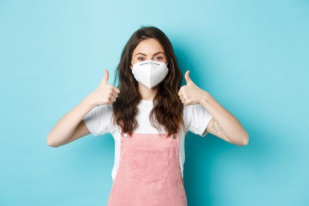 Covid, gezondheid en pandemisch concept. afbeelding van een schattige jonge vrouw met een gasmasker die duimen opsteekt, denkend aan persoonlijke veiligheid tijdens quarantaine, gezichtsmasker, blauwe achtergrond.