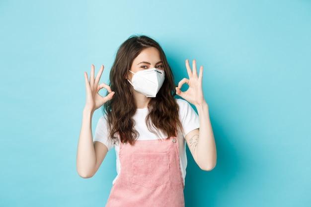Covid, gezondheid en pandemisch concept. heel goed. jonge ondersteunende vrouw die een medisch beademingsapparaat draagt en goede tekens toont ter goedkeuring, prijst het dragen van gezichtsmaskers op een openbare, blauwe achtergrond.