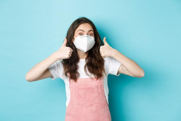 Covid, gezondheid en pandemisch concept. vrolijke jonge vrouw in gasmasker met duimen omhoog in goedkeuring, iets aanbevelen, staande tegen een blauwe achtergrond.