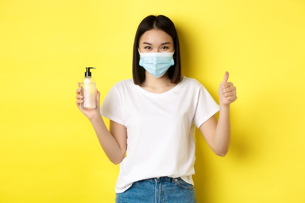 Covid, gezondheidszorg en pandemisch concept. aziatisch meisje in gezichtsmasker van coronavirus, duim opdagen en goed handdesinfecterend middel, staande op gele achtergrond.