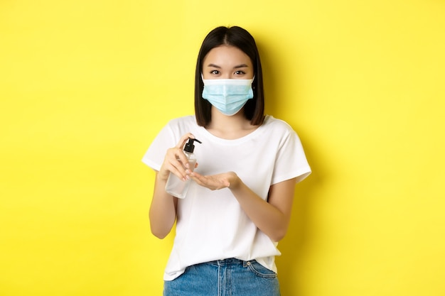 Covid, gezondheidszorg en pandemisch concept. leuke aziatische vrouw in medisch masker die handdesinfecterend middel gebruikt om palm te desinfecteren, die zich over gele achtergrond bevindt.