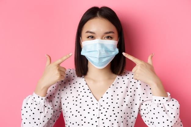 Covid pandemie en lifestyle concept kawaii aziatisch meisje wijzend met de vingers naar haar gezichtsmasker met pre...