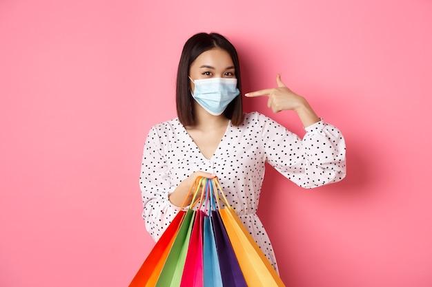 Covid pandemie en lifestyle concept schattige aziatische vrouw met boodschappentassen glimlachend en wijzend naar ...