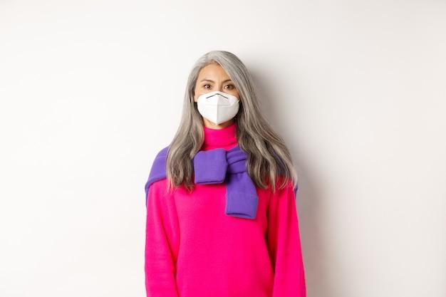 Covid, pandemie en social distancing concept. stijlvolle aziatische senior vrouw die een gasmasker draagt en serieus naar de camera kijkt, staande op een witte achtergrond