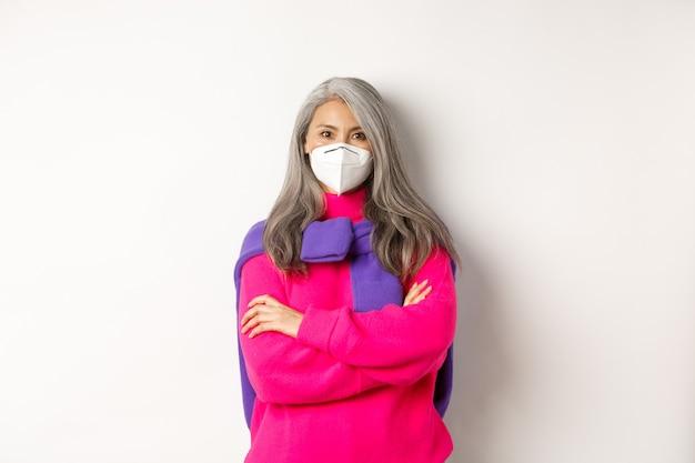 Covid, pandemie en social distancing concept. vastberaden en serieuze aziatische senior vrouw met gezichtsmasker die er zelfverzekerd uitziet, armen gekruist op de borst, staande op een witte achtergrond.