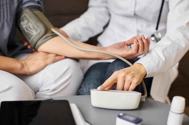 Covid recovery center vrouwelijke arts die de bloeddruk van de oudere patiënt controleert met een apparaat