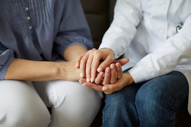 Covid recovery center vrouwelijke arts die de handen van de oudere patiënt
