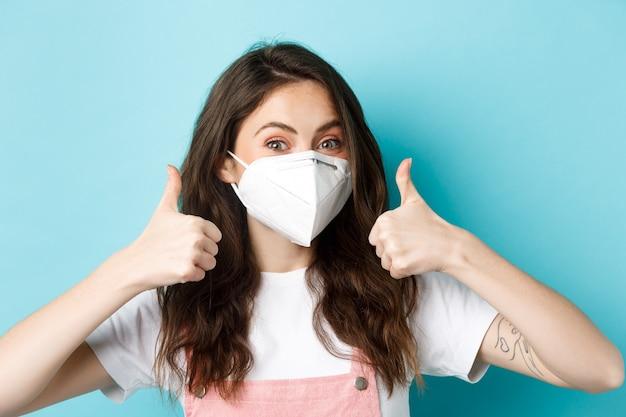 Covid social distancing en lockdown concept jonge vrouw ondersteunt preventieve maatregelen met masker r...