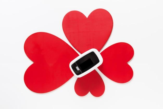 Covid valentijnsdag geschenk concept, pulsoximeter onder bloem van rode harten op witte achtergrond bovenaanzicht