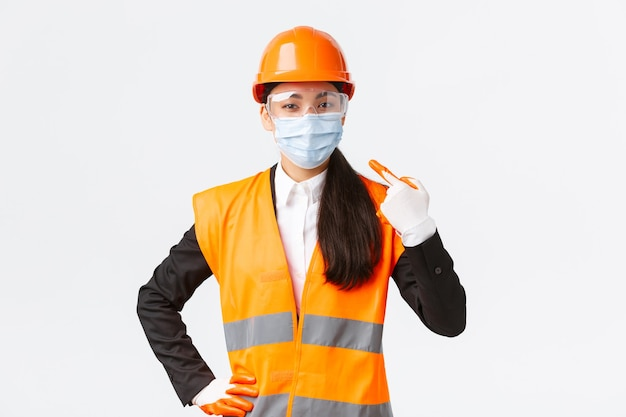 Covid-veiligheidsprotocol bij de constructie van ondernemingen en het voorkomen van virusconcept zelfverzekerde aziatische vrouw ...