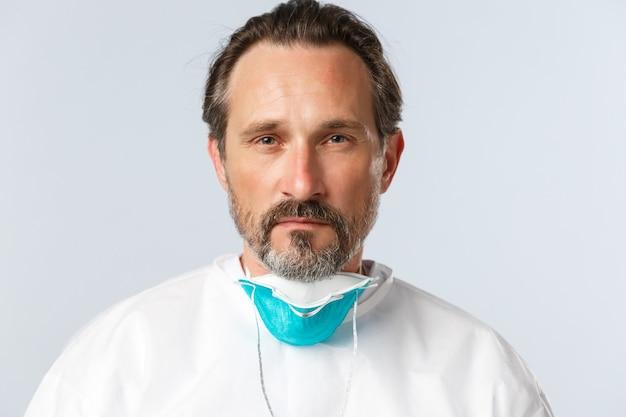 Covid-virus gezondheidswerkers en vaccinatie concept close-up van serieus ogende vermoeide dokter takeof...