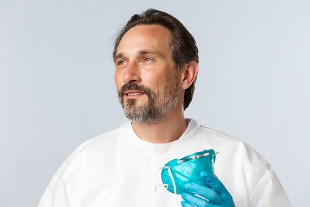 Covid-virus gezondheidswerkers en vaccinatieconcept opgelucht vermoeide lachende arts opstijgen medische...