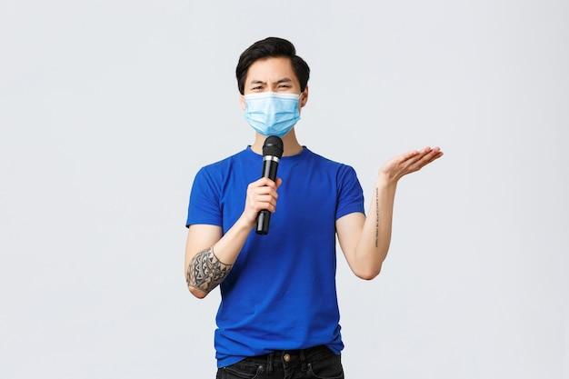 Covid019-levensstijl, mensenemoties en vrije tijd op quarantaineconcept. sceptische en overstuur aziatische man stoorde zich aan slechte nummerkeuze bij karaoke, haalde zijn schouders op met grimassen, gebruikte microfoon om te spreken.