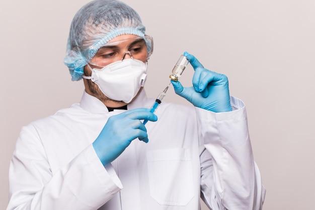 Covid19-besmetting. mannelijke arts onderzoekt geneeskunde voor ziekte, man in blauw masker met spuit en pot