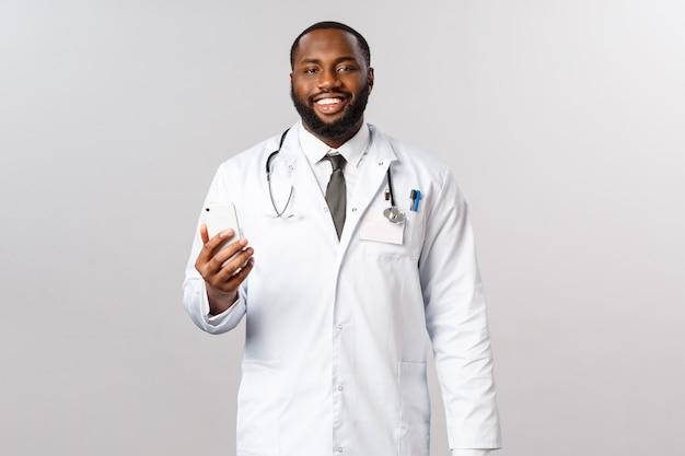 Covid19, pandemie en online geneeskundeconcept. knappe afro-amerikaanse mannelijke arts, arts contact op met zijn patiënten via smartphone-app, glimlachende camera, mensen die thuis blijven maar gebruik maken van de gezondheidszorg