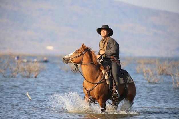 Cowboy die een paard in rivier berijdt