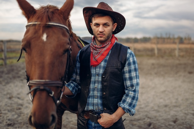 Cowboy poseert met paard op de boerderij van texas