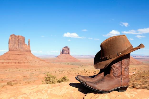 Cowboylaarzen en hoed voor monument valley, vs, panoramisch uitzicht