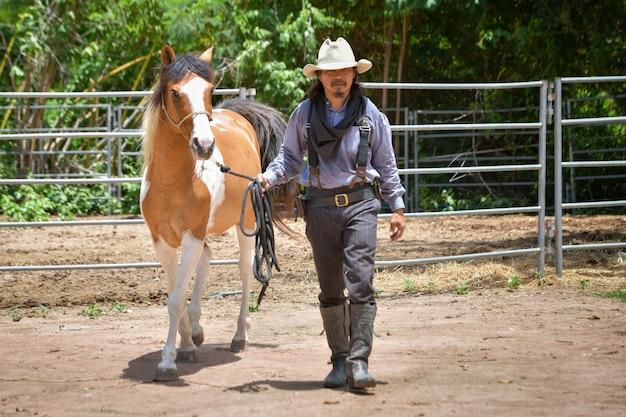 Cowboymannen lopen en leiden een paard op zijn boerderij