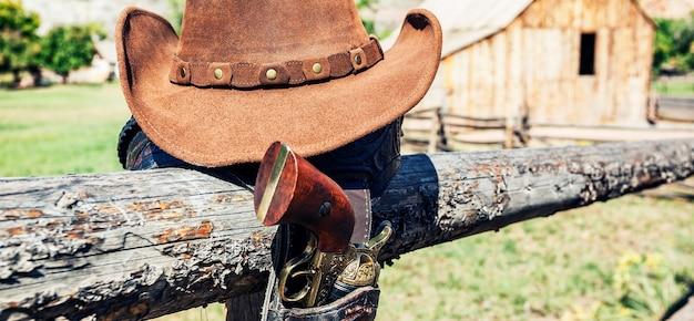 Cowboypistool en hoed buiten in een boerderij, panoramisch uitzicht