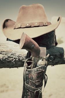 Cowboypistool en hoed buiten in een boerderij