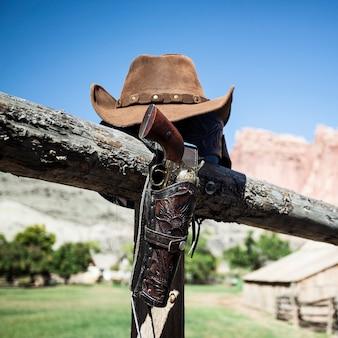 Cowboypistool en hoed buiten onder zonlicht, vs.