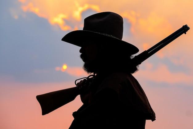 Cowboysilhouet op een paard tijdens aardige zonsondergang