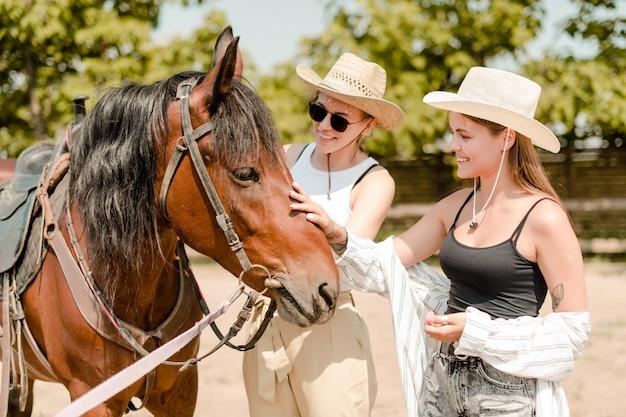 Cowgirls met een paard op een westerse boerderij een paard aan te raken