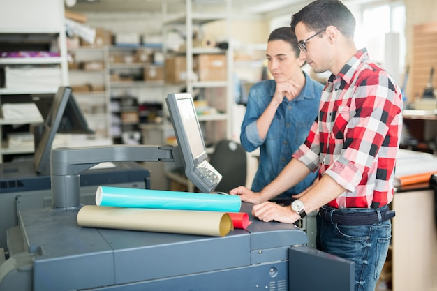 Coworking man en vrouw die printer gebruiken