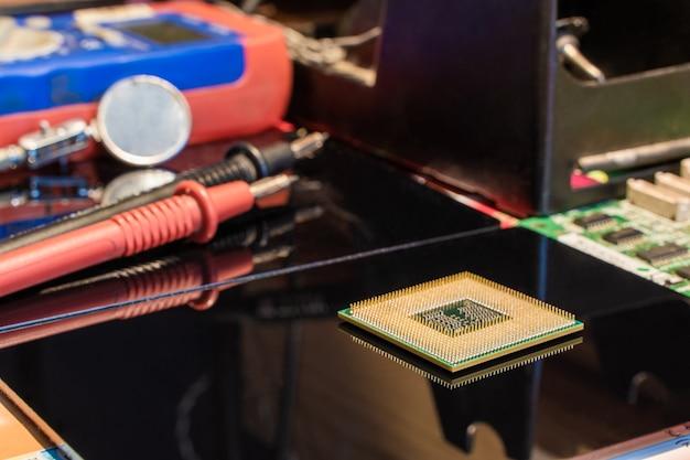 Cpu-processorchip met andere apparatuur op de werkplek van de ingenieur van de zwarte tafel stock photo Premium Foto