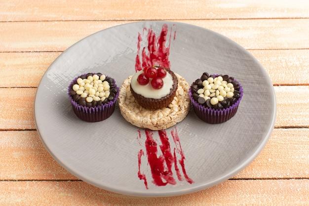Cracker en cake met cranberries bovenop binnen paarse plaat met brownies