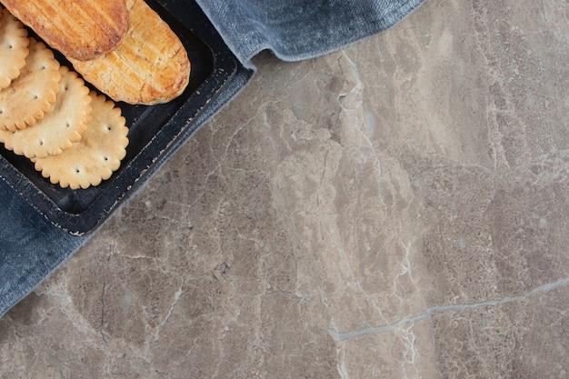 Cracker en zandkoekjes een bord op een handdoek op marmer.